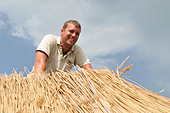 Man working on straw roof - Stock Image - CWWFD7