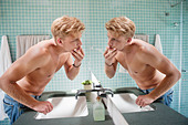 Man looking at himself in mirror - Stock Image - C54BF8
