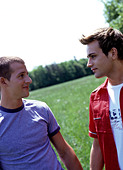 two young gay men in the park holding hands - Stock Image - AAY567