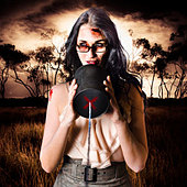 Concept photograph of a female model in devil makeup making a halloween announcement through a tin can phone. Dark haunted - Stock Image - DTKKT9