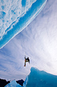 An ice climber swings down from rope to reach face of a large iceberg frozen into Mendenhall Lake, Juneau, Alaska, Winter - Stock Image - CNB373