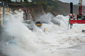 Dawlish, Devon, UK. 13th Nov, 2014. Stormy weather brings waves crashing over trains at Dawlish, Devon, UK, where repairs are still ongoing following damage to the sea wall in February 2014. © Theo Moye/Alamy Live News - Stock Image - EAEBGN