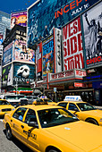 Yellow taxis in Times Square, New York City during daytime. - Stock Image - CRTJXD