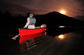 A man canoeing in a red boat at night on a mountain lake in Oregon. - Stock Image - BRJW79