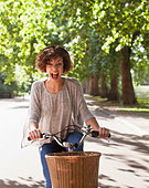 Exuberant woman with mouth open riding bicycle in park - Stock Image - CC9FFR