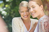 Women smiling together outdoors - Stock Image - E59TPM