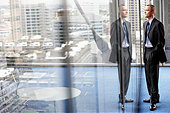 Businessman Standing Beside a Giant Office Window - Stock Image - EDJW3H