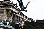 Edinburgh, Scotland, UK. 25th June 2015. Freerunners Chris Martin and Jordan Byrne performing the improvised sport outside the National Galleries of Scotland in Edinburgh. Chris (bottom) is seen here photographing friend Jordan in action with his mobile phone. © Chris Strickland / Alamy Live News - Stock Image - EWFGNY