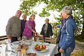 Three senior couples having lunch outdoors, greeting each other - Stock Image - BP6KMK