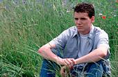 teenage boy sitting in grass   - SerieCVS100019002 - Stock Image - BC39Y9