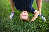 A mother holds her son upside down by his feet while he laughts in the backyard of their home. - Stock Image - B706BN