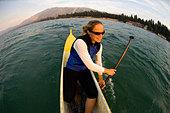 Woman Steering a Canoe, Lake Tahoe, California - Stock Image - BA8H4X