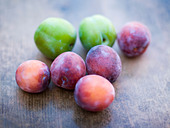 Green and purple plums on wooden table - Stock Image - C1PADJ