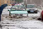 Shanghai. 24th Aug, 2015. Cars run on a waterlogged road in east China's Shanghai, Aug. 24, 2015. Shanghai witnessed gales and rainstorms since Sunday night under the influence of the approaching typhoon Swan. © Zhao Yun/Xinhua/Alamy Live News - Stock Image - F108WG