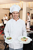 Portrait of smiling chef holding salad and entree - Stock Image - CWJPR0