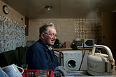 Senior single man watching a kettle boil in his motor home - Stock Image - BJ90YC