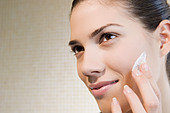 Woman applying moisturiser - Stock Image - A78H1K
