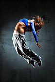 Young woman dancer jumping. On wall background. - Stock Image - BXAG10
