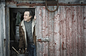 An organic farm in upstate New York in winter A man at an open barn door - Stock Image - DT1YP7