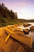 A canoe with paddle at sunrise, during summer, on the shore of Booth Lake, Algonquin Provincial Park, Ontario, Canada. - Stock Image - CFAD3G