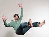 Man falling against grey background, mouth open, portrait - Stock Image - C3PK6G