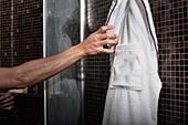 Man reaching for bathrobe in shower - Stock Image - CWWFGK