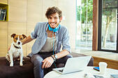 Man petting dog in office - Stock Image - E59HM0