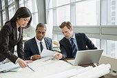 Business people reviewing blueprints at desk - Stock Image - DXPK8C