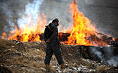 Kabul, Afghanistan. 29th Oct, 2014. An Afghan policeman stands guard beside burning drugs in Kabul, Afghanistan, on Oct. 29, 2014. The government of Afghanistan set on fire 20 tons of narcotics in the outskirts of Kabul on Wednesday. © Ahmad Massoud/Xinhua/Alamy Live News - Stock Image - E9K9XN