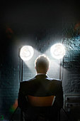 Interrogation scene with spotlights shining in a man's face - back view of restrained businessman - Stock Image - AKTJWJ