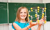Smiling schoolgirl holding molecular model in classroom, portrait - Stock Image - CWYJ37