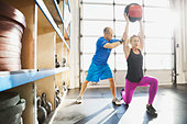 Gym instructor assisting woman with medicine ball lunge - Stock Image - DN95RE