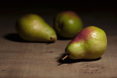 still life of three Comice pears on wood background - Stock Image - AJ21F2