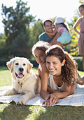 Mother, daughter and dog laying in grass - Stock Image - DAM71Y