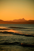 The afternoon break at sunset at Wategos beach Byron Bay Australia with  Mount Warning in the background. - Stock Image - AHEWNE