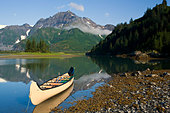 A canoe sits in waiting on a sunny day on the Lower Pedersen Lagoon, Kenai Fjords National Park. - Stock Image - BX544X