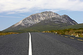 open road at Errigal mountain donegals highest peak against a blue sky between dunlewey and letterkenny - Stock Image - AJAWN4