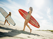 USA, New York State, Rockaway Beach, Two women carrying surfboards on beach - Stock Image - D26XP6