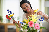 African American woman arranging flowers - Stock Image - BN8NYB
