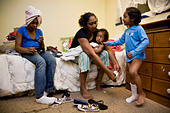 Selena Pina, a homeless mother of four, gets her children dressed for school at the Family Promises Center in Sacramento, CA. - Stock Image - BDHKN0