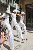 Three girls dancing on stilts in street Old Havana Cuba - Stock Image - DXGY8W