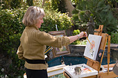 A woman standing in front of an easel, enjoys plein air painting in a suburban garden. - Stock Image - AJJKJT