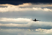 Plane in flight in a dramatic cloudscape. - Stock Image - BEGR0K