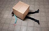 Teenage girl lying under cardboard box - Stock Image - CT0W98