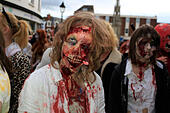 """Glastonbury, Somerset, UK. 25 October 2014: Zombie hoards gather at Glastonbury for  annual Zombie walk where participants  dressed as marauding zombies lurch along the high street turning willing victims into the """"undead""""  This is the third annual Glastonbury Zombie Walk and is hosted by local charity, Martha Care, with all proceeds going toward supporting families with very sick children. © Tom Corban/Alamy Live News - Stock Image - E9D5K2"""