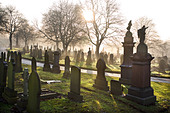 Low winter sunlight flooding through a misty cemetery in Stoke on Trent Staffordshire UK - Stock Image - A2RD8Y