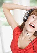 Woman wearing headphones and dancing - Stock Image - B0KAW9