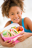 Young girl holding packed lunch in living room smiling - Stock Image - B3K60F
