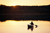 Woman paddling a canoe. - Stock Image - ACE3TJ