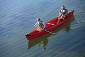 Couple paddle canoe on lake - Stock Image - AB0HXY